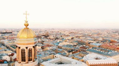 Aerial flight near the golden dome with a cross of St. Isaacs Cathedral at sunset. Amazing view of St. Petersburg