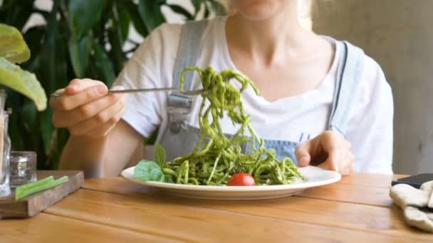 Mädchen gibt frischen rohen Gemüsesalat auf Silbergabel