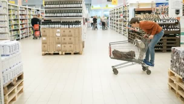 cheerful buyer man riding on a cart among the products in the supermarket