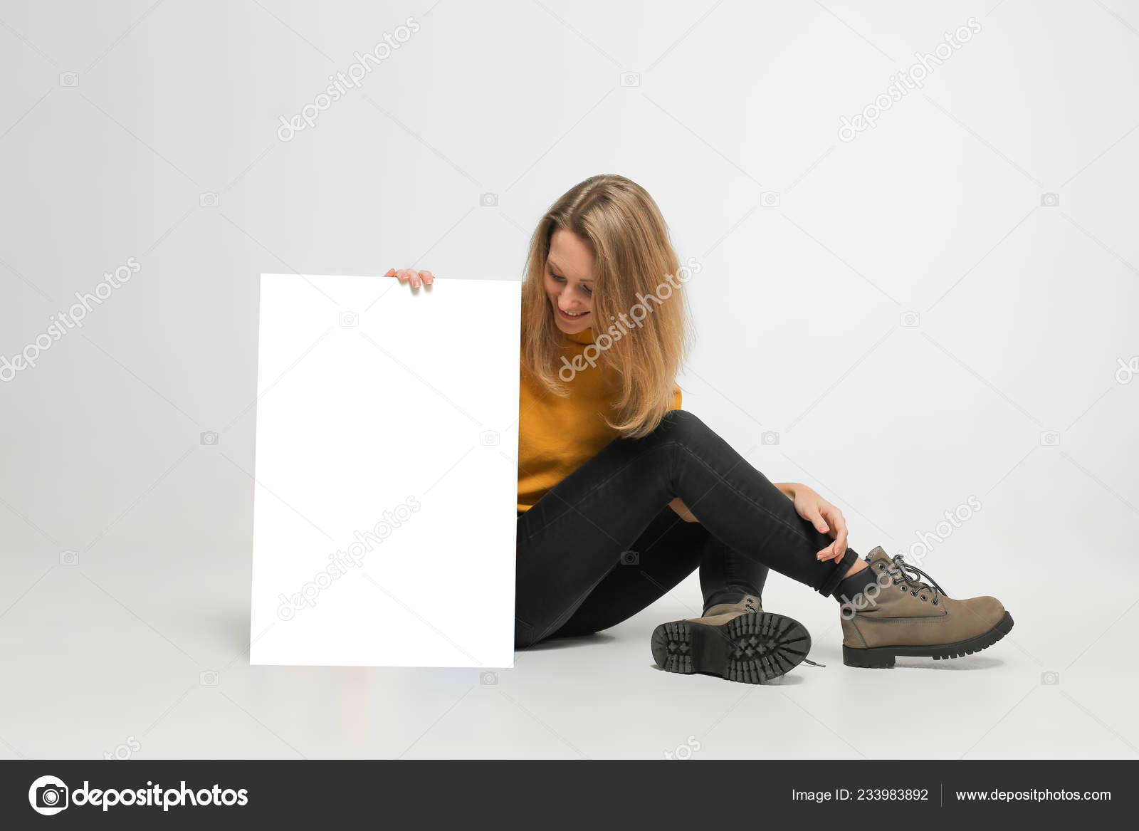 ... woman with blond hair, wearing casual outfit, boots, is sitting on white floor, holding white makeup poster, isolated on white background — Photo by Bo.