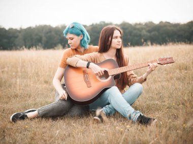 Two women sitting on the field and play the guitar. Best friends