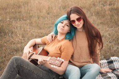 Two young women lie on the field and play the guitar