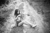 Young woman playing the violin in the forest