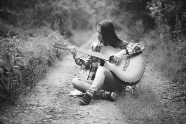 Young woman plays guitar in the forest. Black and white