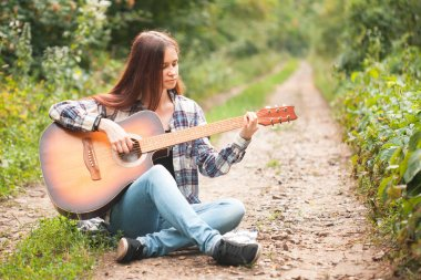 Adorable woman plays guitar in the forest