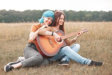 Two beautiful women sit on the grass and play the guitar.