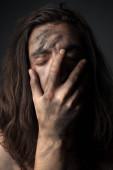 Fotografie Porträt eines unglücklichen jungen Mannes in Ruß. Hand aufs Gesicht