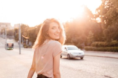 Happy young woman walkinng on the street under sunset light