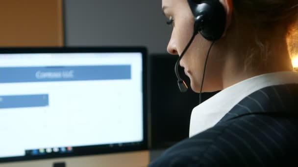 Call centrum operátor přijme volání a komunikuje s klientem. Pohled zezadu