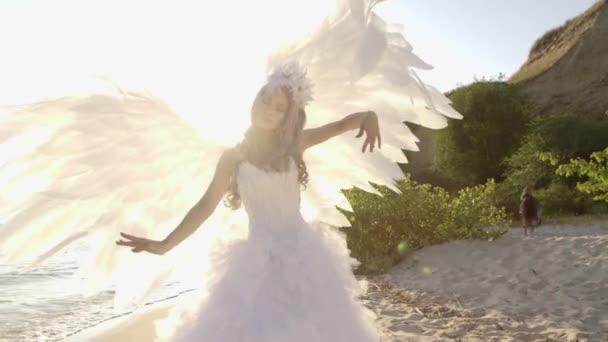 Delicate beautiful blonde woman posing with angel wings seashore