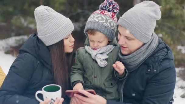 Family with son looks at the photo on the phone in the winter forest. Happy xmas