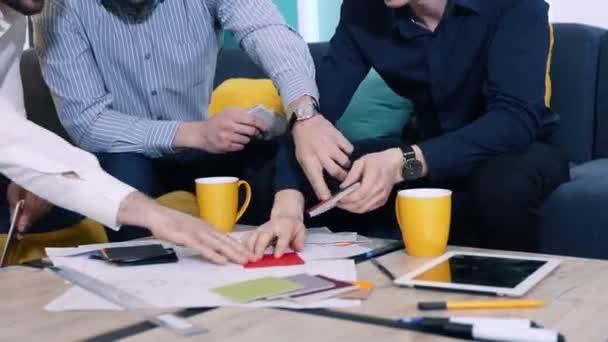 Kollégák férfi munka felületi választani a minták hivatalban. Közeli kép: kezek.
