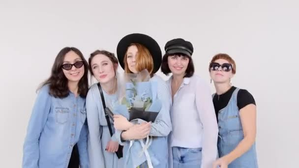 Skupina žen v Džínové Oblečení pózuje v bílé studio. Banda květiny v jejich rukou. Ženy v brýle a klobouky