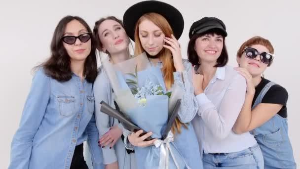 Un gruppo di donne in vestiti del denim in posa in uno studio di bianco. Un mazzo di fiori nelle loro mani. Donne in vetri e cappelli