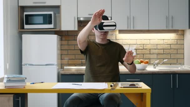 Young man puts on virtual reality glasses and works sitting on the kitchen at home.