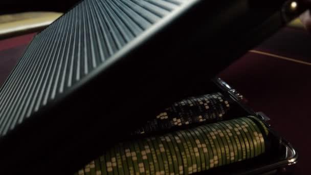 Prodejce se otevře kufr s poker žetony v kasinu. Detail rukou. Poker žetony pro hazardní karetní hra