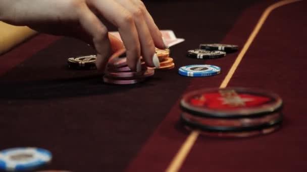 Hrát poker. Žena je nervózní, Prstění čipy v ruce na pokerovém stole. Ruční zblízka. Casino gamble.