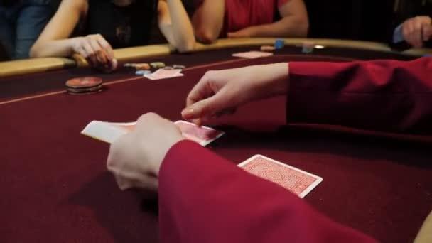 Mettere le carte sul tavolo rosso, gioco di poker, gioco dazzardo, close-up mani dealer del casinò. Giocatori su priorità bassa.