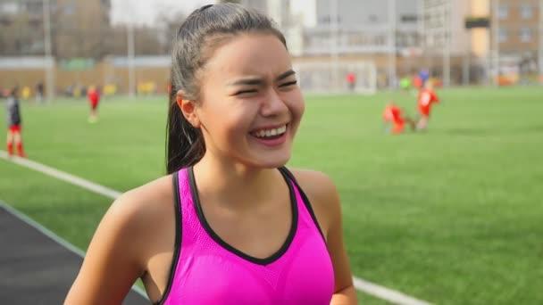 Ázsiai futó lány nevetett a stadion a kezdete előtt portréja.