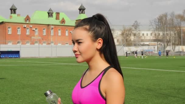 Asian young sporty girl with bottle of water in hands is walking on stadium after training.