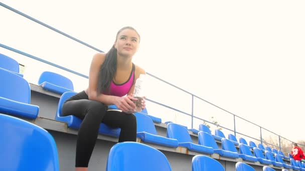 Young asian athlete girl is resting sitting at the stadium on a sunny day.