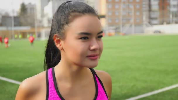 Athletic asian young girl is running on stadium. Fitness, sports concept.