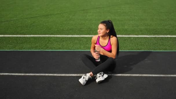 Sporty asian girl in sportswear is sitting on the stadium after training.