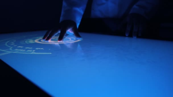 Man indicators on sensor touch screen sensory interactive table in the dark.