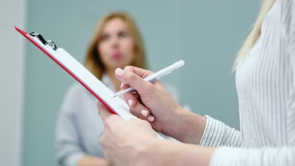 Psychologist is conducting the evaluation test of the survey with patient and writes the result. Hands close-up.