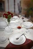 Restaurace podává tabulka s bílé nádobí, příbory a pohárky