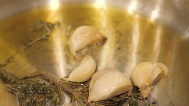 Detailní záběr stroužky česneku, smažené v oleji s kořením a bylinné oleje na pánev