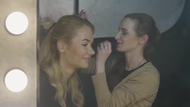 Woman visagiste applying waterproof makeup for beautiful girl in beauty salon