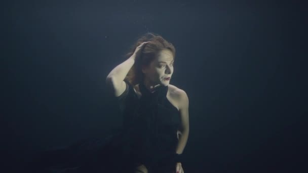 Attractive woman swimming under water in dark pool while video shooting