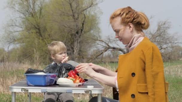 Mladá matka krájení zeleniny u stolu během pikniku a malý syn