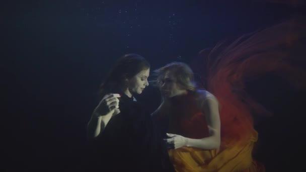 Dvě sexy žena v šifónové šaty dohromady plavání pod vodou v tmavý fond