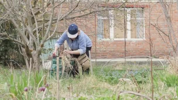 Vezető nő tisztító száraz fű, kerti háztáji kertészeti munka közben