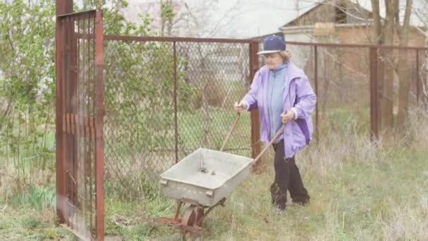 Stará žena zahradník s prázdnou zahradní vozík na Zahradní dvorek
