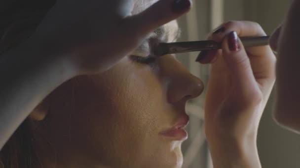 Makeup artist using cosmetics brush for applying eye shadow on eyelid