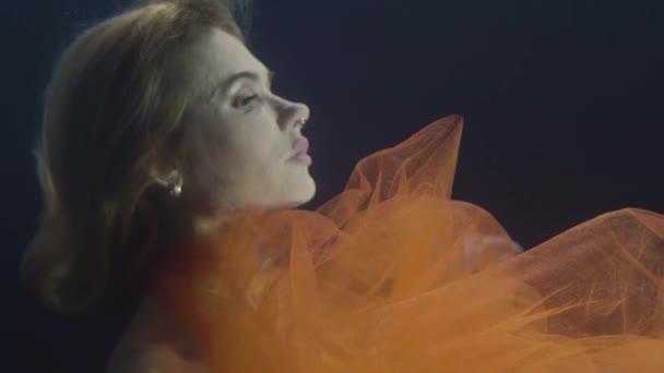 Mořská panna žena v šifónové šaty, plavání pod vodou na tmavém pozadí