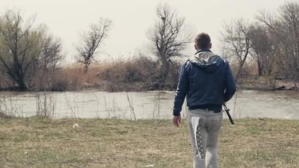 Fiatal ember, horgászbot, séta a folyó partján hátsó nézet