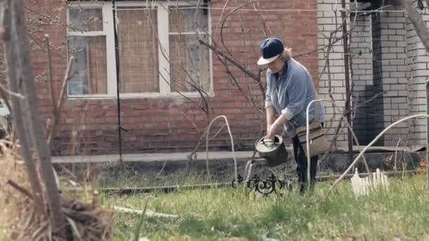 Starší žena zalévání rostlin od zalévání květináč v zahradním dvorku