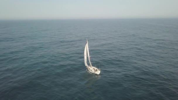 Jacht a kék tengerre légi úszó fehér vitorla. Drámai táj