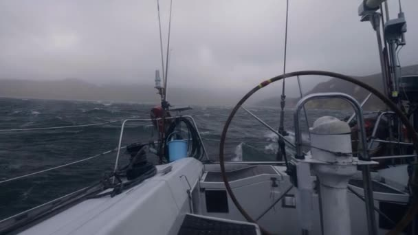 View from board yacht sailing on stormy sea waves. Sail boat swinging on waves