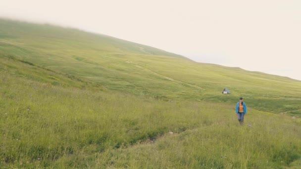 Turistické žena chůze na zelené louce na hory a kopce krajiny