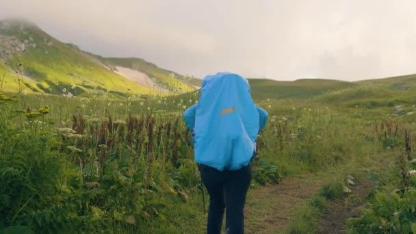 Turistické lidí s batoh cestujete na zelené louce horské údolí