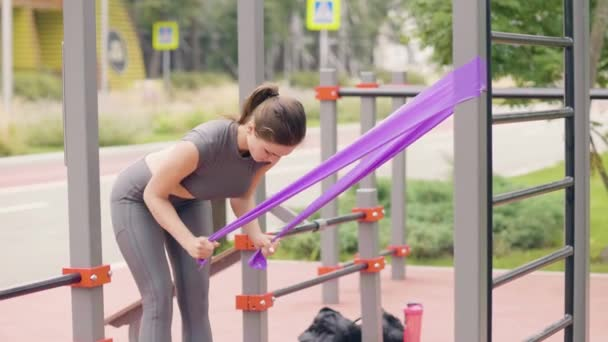 Mladá žena, která dělá fitness cvičení s expandér sport na sportovní hřiště
