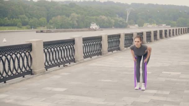 Fitness žena pomocí sportu expandér pro venkovní trénink cvičení. Aktivní životní styl