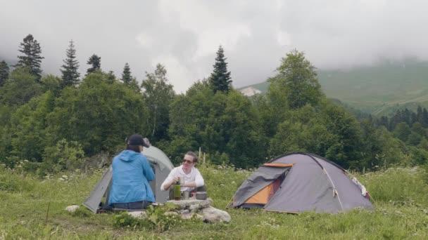 Muž a žena odpočívá na stan a horské krajiny zázemí