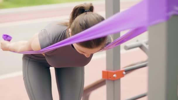 Atlet žena pomocí sportu expandér pro venkovní fitness trénink v letním parku