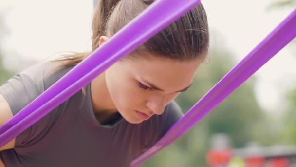 Žena fitness trénink s sport expandéru v letním parku zblízka